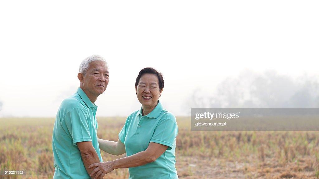 Portrait of Asian senior couple on bright green background : Foto de stock