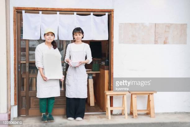 アジアのカフェスタッフとしてのアジア女性の肖像 - のれん ストックフォトと画像