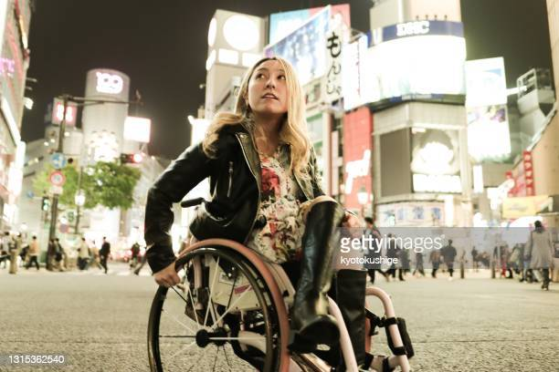 portrait of asian woman has a wheelchair solo travel in the night - tokyo japan stock pictures, royalty-free photos & images