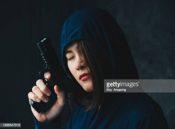 portrait of asian woman in blue hood closed her eyes while holding a gun in her hand. - gun control stock pictures, royalty-free photos & images