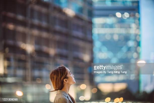 portrait of asian woman looking up to sky with confidence against illuminated city buildings at dawn - anticipación fotografías e imágenes de stock