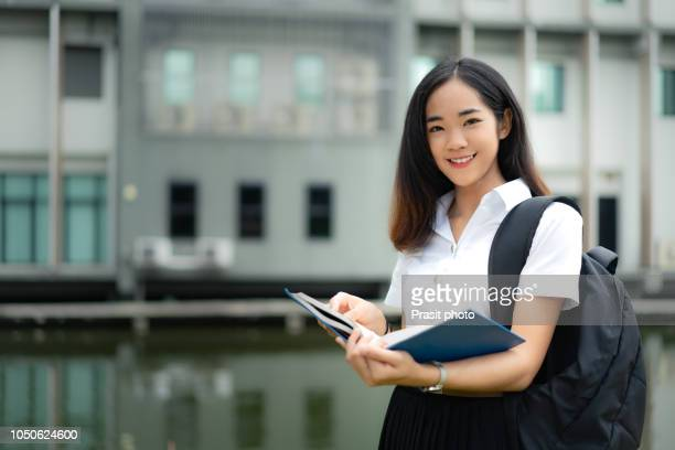 portrait of asian woman university studnt in uniform standing and holding book outdoors at campus. - stipendium stock-fotos und bilder