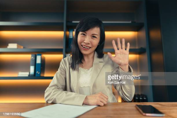portrait of asian woman waving at the camera during a web call - greeting stock pictures, royalty-free photos & images