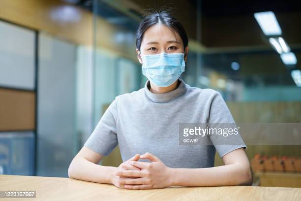 portrait of asian woman with protective face mask in office - 感染症 ストックフォトと画像