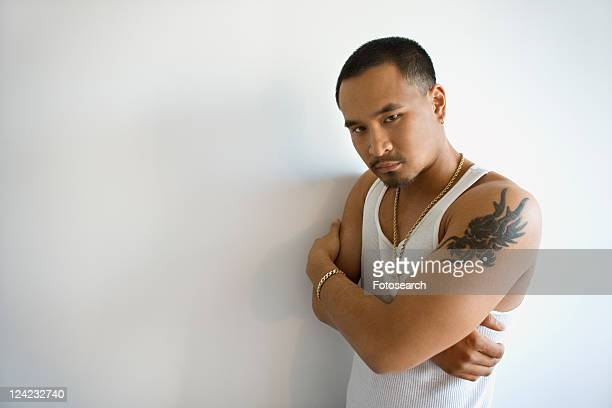 Portrait of Asian young adult man leaning against white wall with arms crossed looking at viewer.