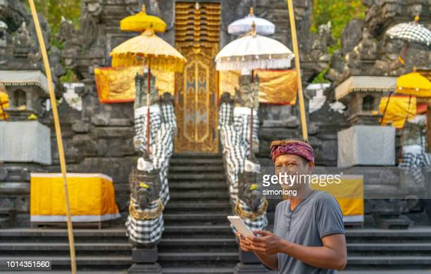 Portrait of  Asian young man using digital tablet in front of temple. Bali,Indonesia.