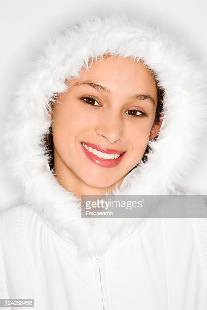 portrait of asian-american teen girl wearing fur lined coat hood and smiling against white background. - young hairy pics stock photos and pictures
