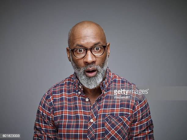 portrait of astonished man wearing spectacles and checked shirt in front of grey background - überraschung stock-fotos und bilder