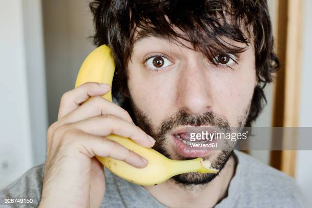 portrait of astonished young man telephoning with banana - konzepte und themen stock-fotos und bilder