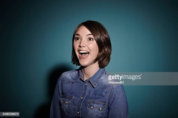 portrait of astonished young woman in front of blue background - überraschung stock-fotos und bilder