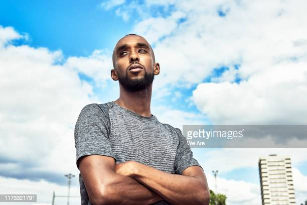 portrait of athlete against cloudy sky - low angle view stock pictures, royalty-free photos & images