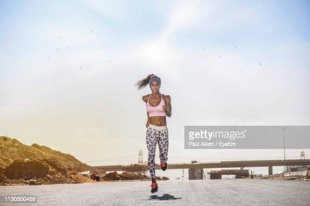 portrait of athlete running on road against sky during sunny day - aikāne stock pictures, royalty-free photos & images