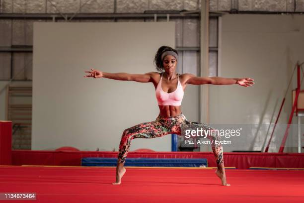 portrait of athlete with arms outstretched exercising in gym - aikāne stock pictures, royalty-free photos & images