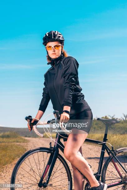 Portrait of athlete with cycling helmet holding on to racing bicycle