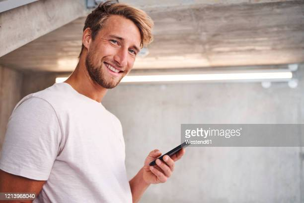 portrait of attactive young man wearing white t-shirt holding smartphone - alleen één jonge man stockfoto's en -beelden