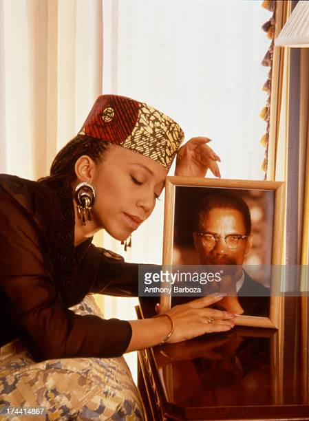 Portrait of Attallah Shabazz as she poses with a framed portrait of her father minister and Civil Rights activist Malcolm X late twentieth century
