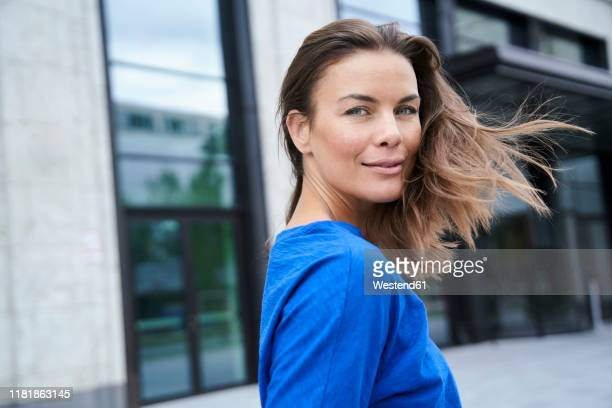 portrait of attractive brunette woman in the city turning round - one mature woman only stock pictures, royalty-free photos & images