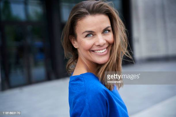 portrait of attractive brunette woman wearing blue top in the city - einzelne frau über 40 stock-fotos und bilder