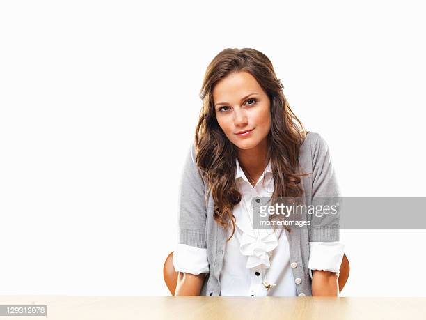 Portrait of attractive business woman sitting with hands under table