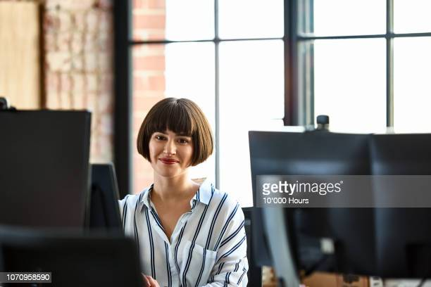 portrait of attractive businesswoman smiling at work - kurzes haar stock-fotos und bilder