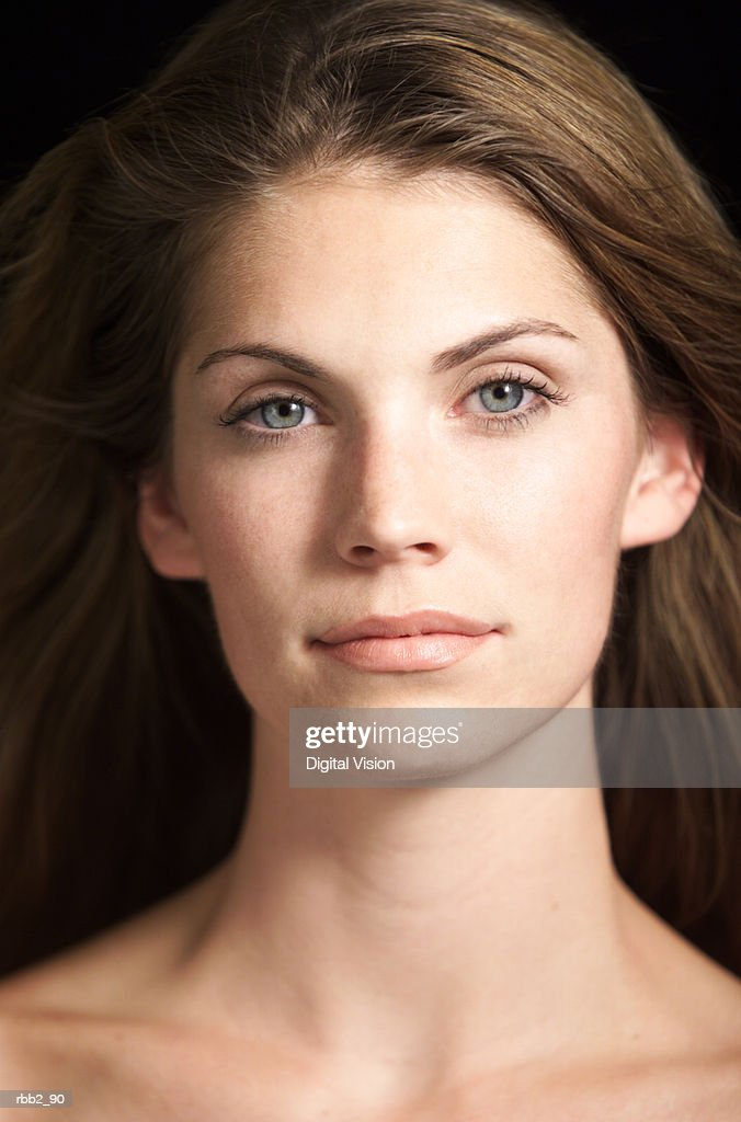 portrait of attractive caucasian woman with blue eyes and hair flowing in wind looks at camera : Stock Photo