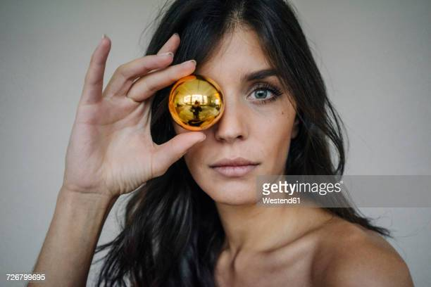 Portrait of attractive dark-haired young woman holding Christmas bauble
