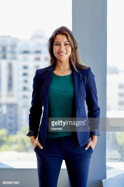 Portrait of attractive female executive standing in creative office. Smiling businesswoman is with hands in pockets against window. She is wearing smart casuals.