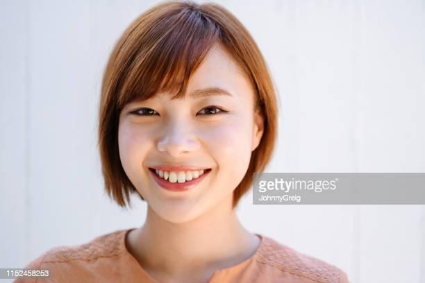 カメラで微笑む魅力的な日本人女性のポートレート - 美しい人 ストックフォトと画像