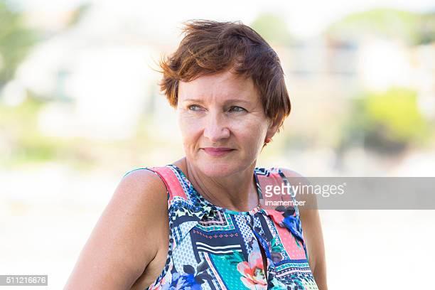 Portrait de jolie femme d'âge mûr avec Zone rouge courte cheveux, extérieur