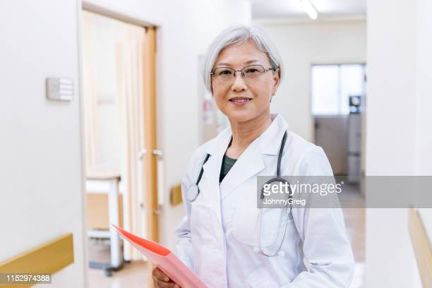 portrait of attractive senior female doctor holding notes - female doctor stock pictures, royalty-free photos & images