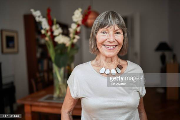 portrait of attractive senior woman at home - seniore vrouwen stockfoto's en -beelden
