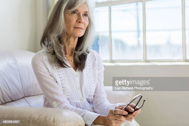 portrait of attractive senior woman sitting in apartment - 65 69 jahre stock-fotos und bilder