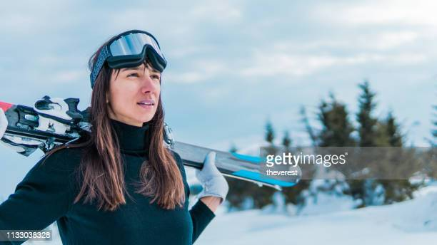 portrait of attractive skier with ski goggles holding skies - ski wear stock pictures, royalty-free photos & images