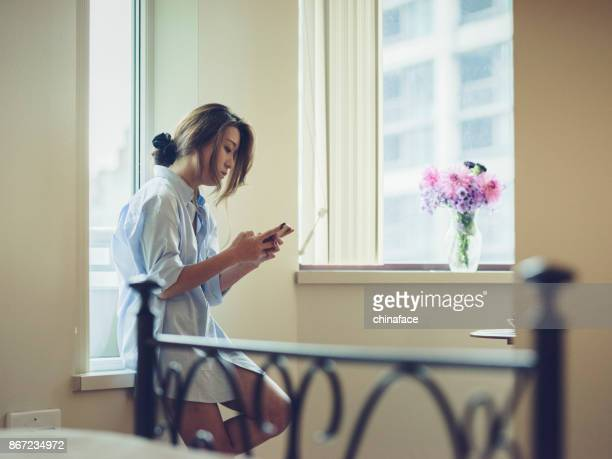 portrait of attractive woman using phone by window