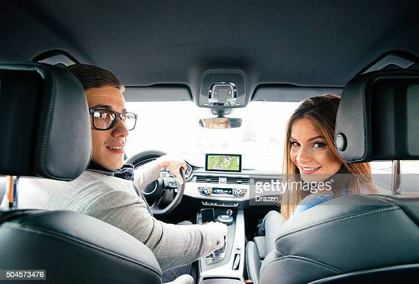 Portrait of attractive young couple driving luxury car in city