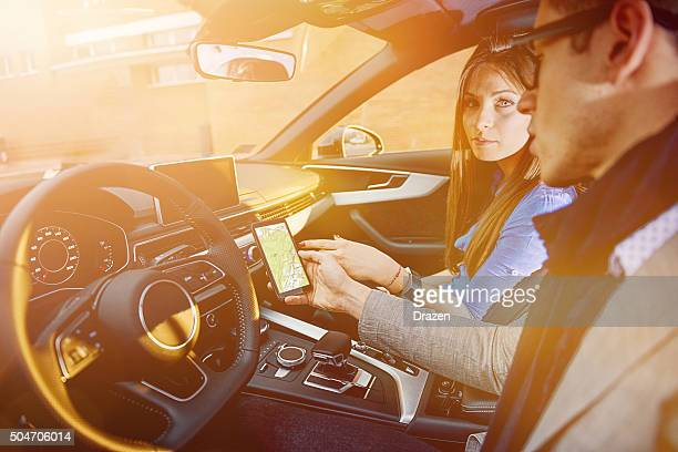 portrait of attractive young couple driving luxury car in city - status car stock pictures, royalty-free photos & images