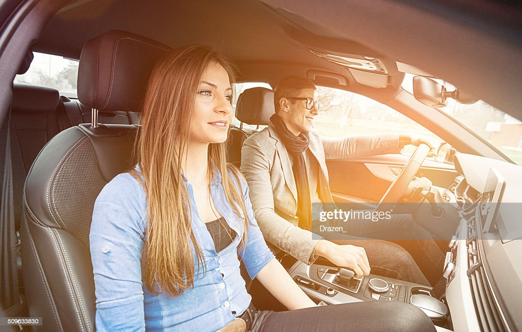 portrait de s duisante jeune couple conduire une voiture de luxe de la ville photo getty images. Black Bedroom Furniture Sets. Home Design Ideas