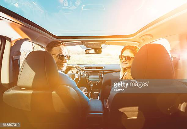 Portrait of attractive young couple driving luxury car in nature