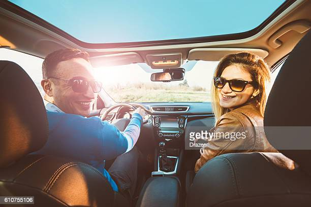 Portrait of attractive young couple driving SUV in nature