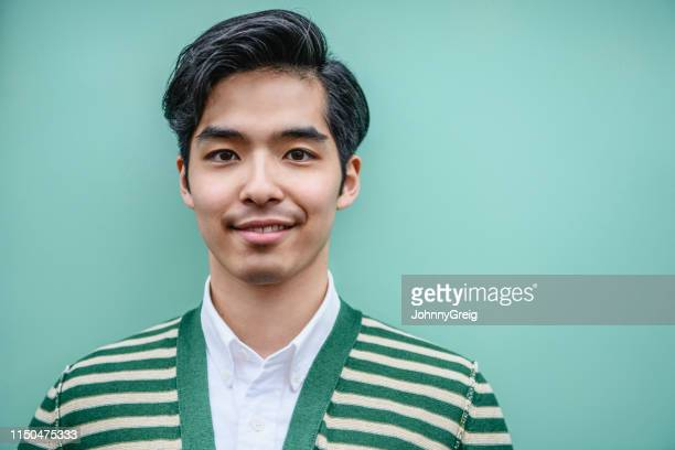 portrait of attractive young japanese man in green and white striped cardigan - mint green stock pictures, royalty-free photos & images