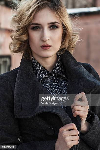 Portrait of attractive young woman wearing long coat outdoors