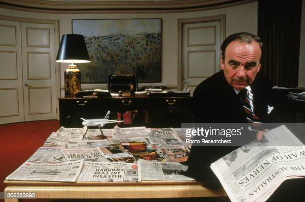 Portrait of Australian media executive Rupert Murdoch as he poses, on a table covered in newspapers, in his office, Australia, 1982.