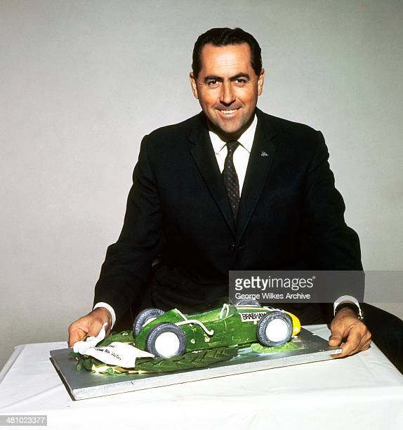 Portrait of Australian racing car driver Sir Jack Brabham AO OBE as he poses with a model of a Formula One car London England 1969