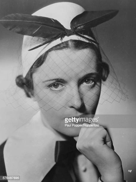 Portrait of Austrian actress Jenny Jugo wearing a feather hat with a veil circa 1935