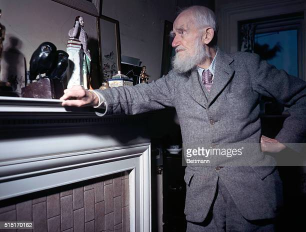 Portrait of author George Bernard Shaw at home gazing at mantlepiece