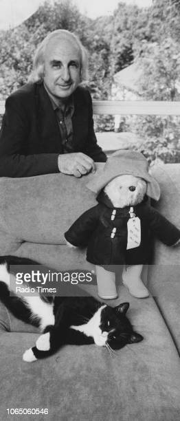 Portrait of author Michael Bond with a pet cat and a toy of his most famous character Paddington Bear, August 1976.