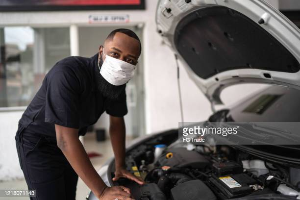 portrait of auto mechanic man with face mask at auto repair shop - mechanic stock pictures, royalty-free photos & images