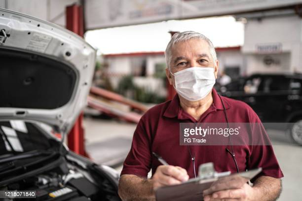 portrait of auto mechanic senior man with face mask at auto repair shop - garage stock pictures, royalty-free photos & images
