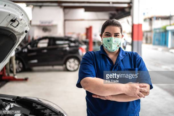 portrait of auto mechanic woman with face mask at auto repair shop - essential workers stock pictures, royalty-free photos & images