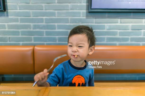 Portrait of baby boy eating food with fork